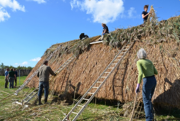 Masamuda volunteers work on roofing the reconstructed house
